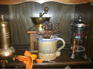 Statue of Caffeina rising from a coffee cup, which is between a coffee press and a hand coffee grinder. Another hand coffee grinder is behind the statue and a tiger lily blossom is before it.